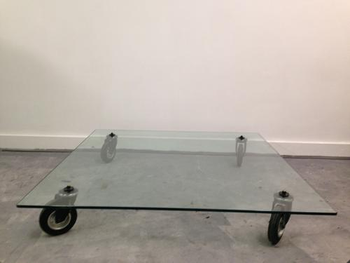 Low glass coffee table on industrial wheels