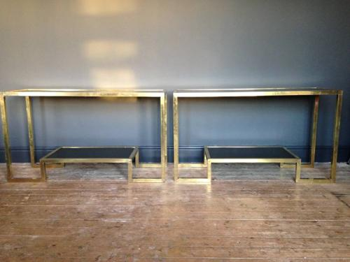 A pair of brass and glass console tables