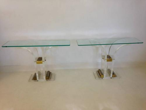 A pair of lucite and brass console tables