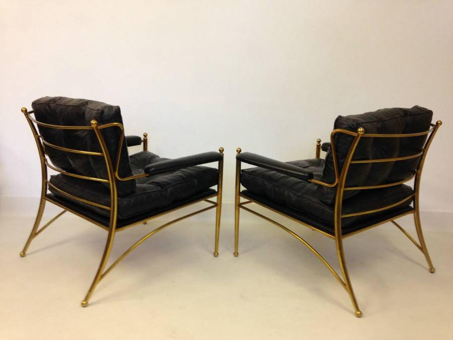 A pair of brass framed and leather armchairs