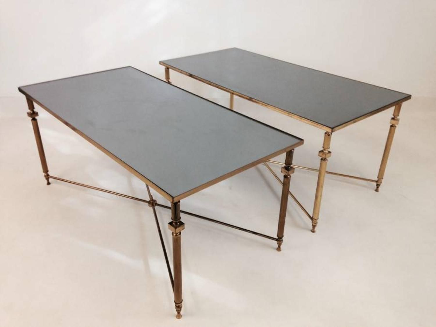A pair of brass and black glass coffee tables