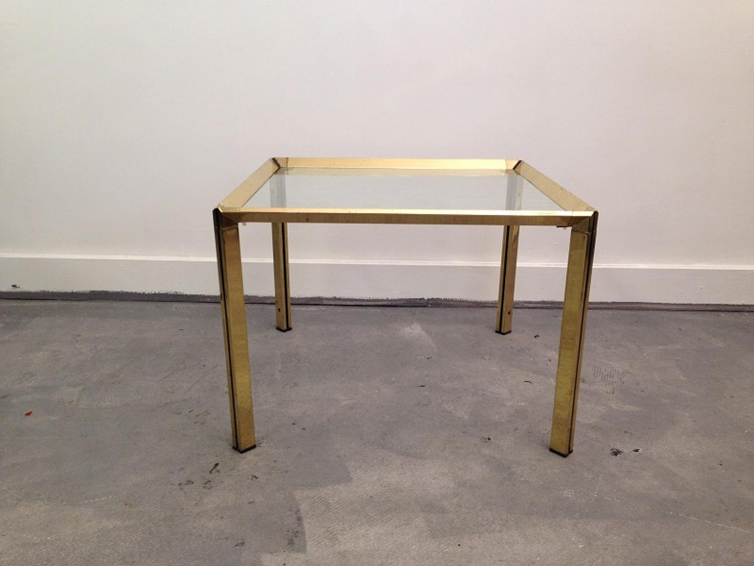 A brass and glass lamp or side table