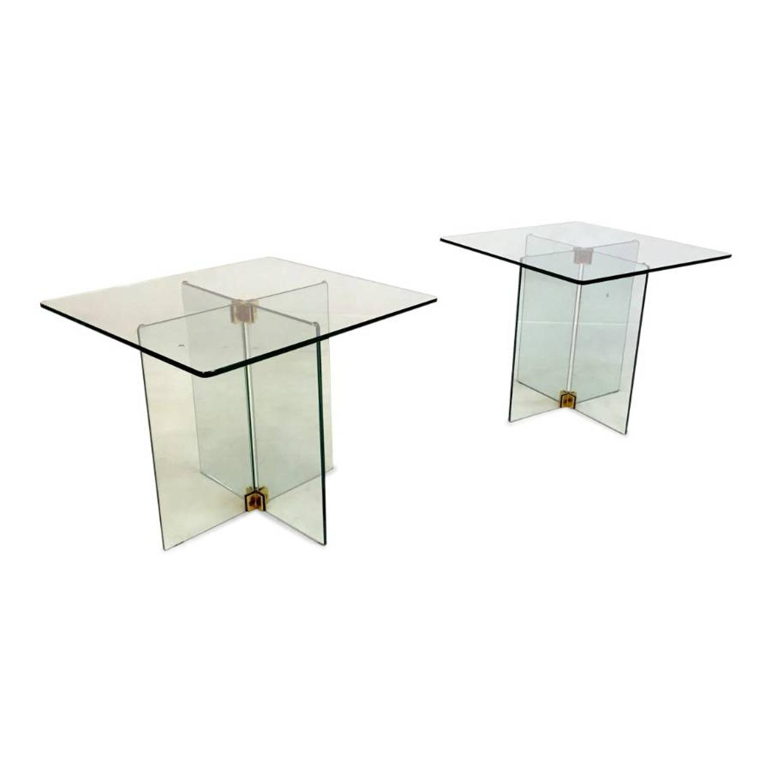 A pair of glass and brass side tables
