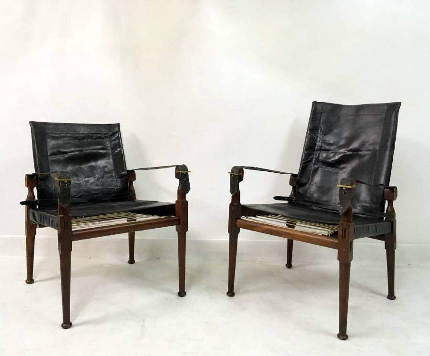 A pair of black leather and rosewood safari chairs