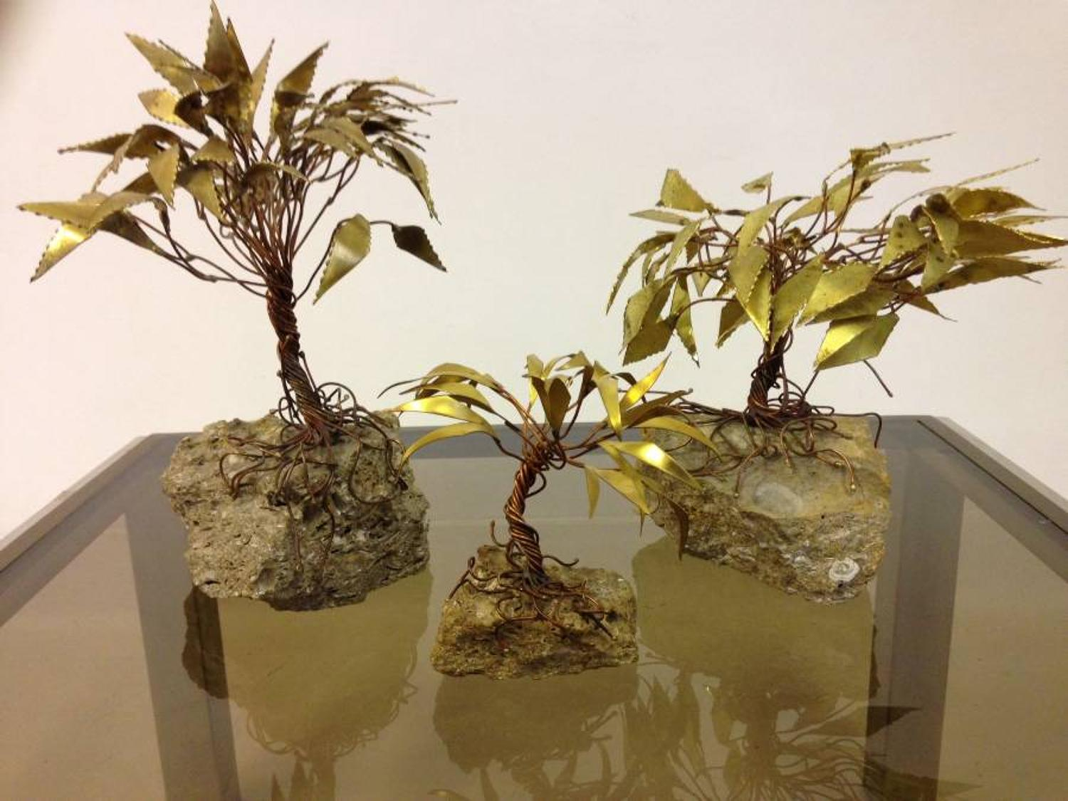 A trio of brass and copper tree sculptures