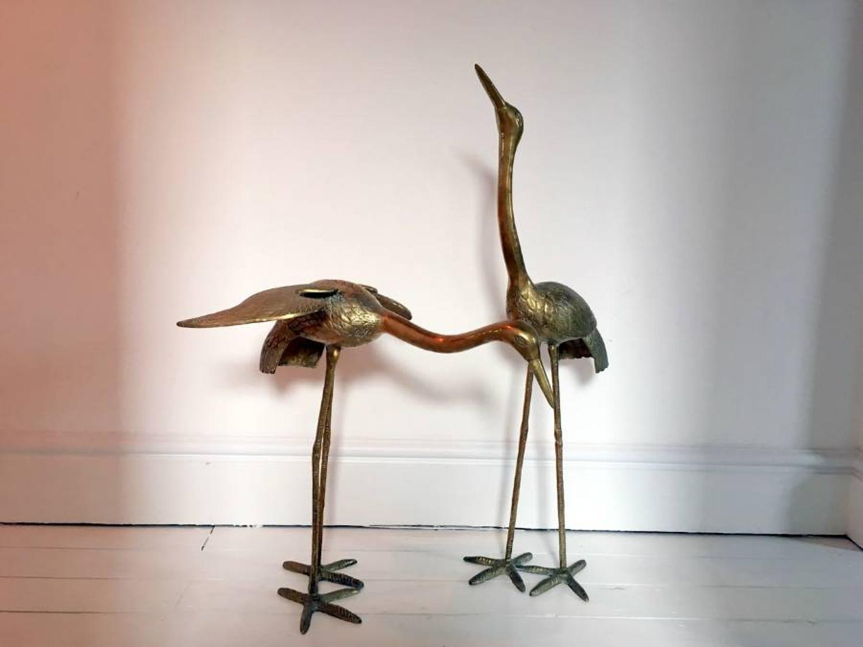 A pair of freestanding brass birds
