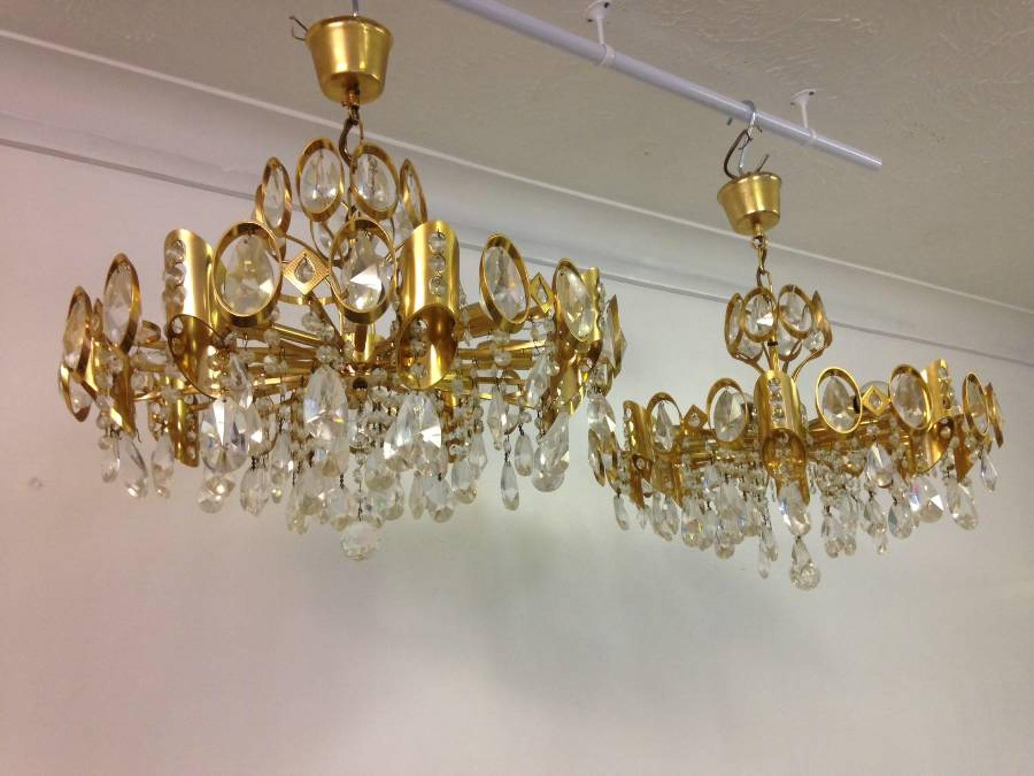 A pair of gilt brass and crystal chandeliers