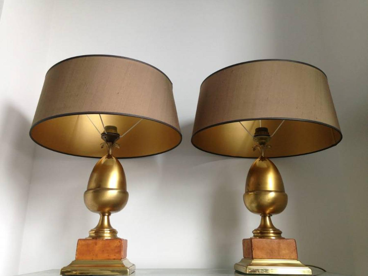 A pair of brass acorn and leather lamps