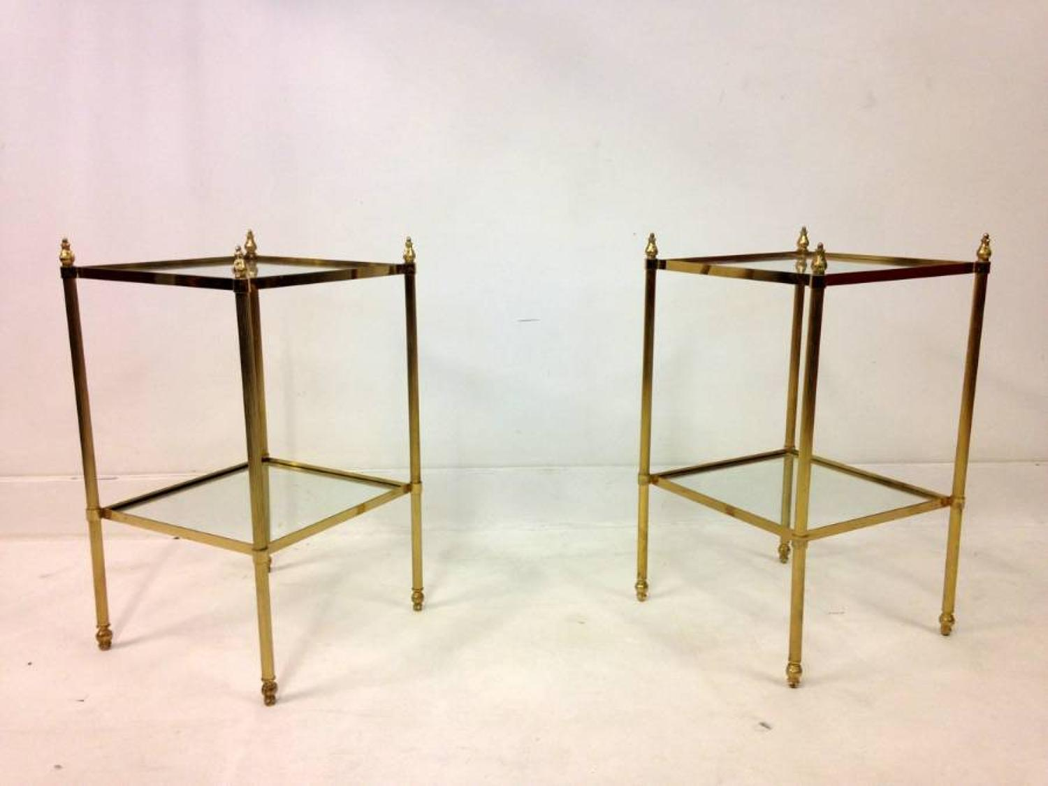 A pair of brass and glass side tables