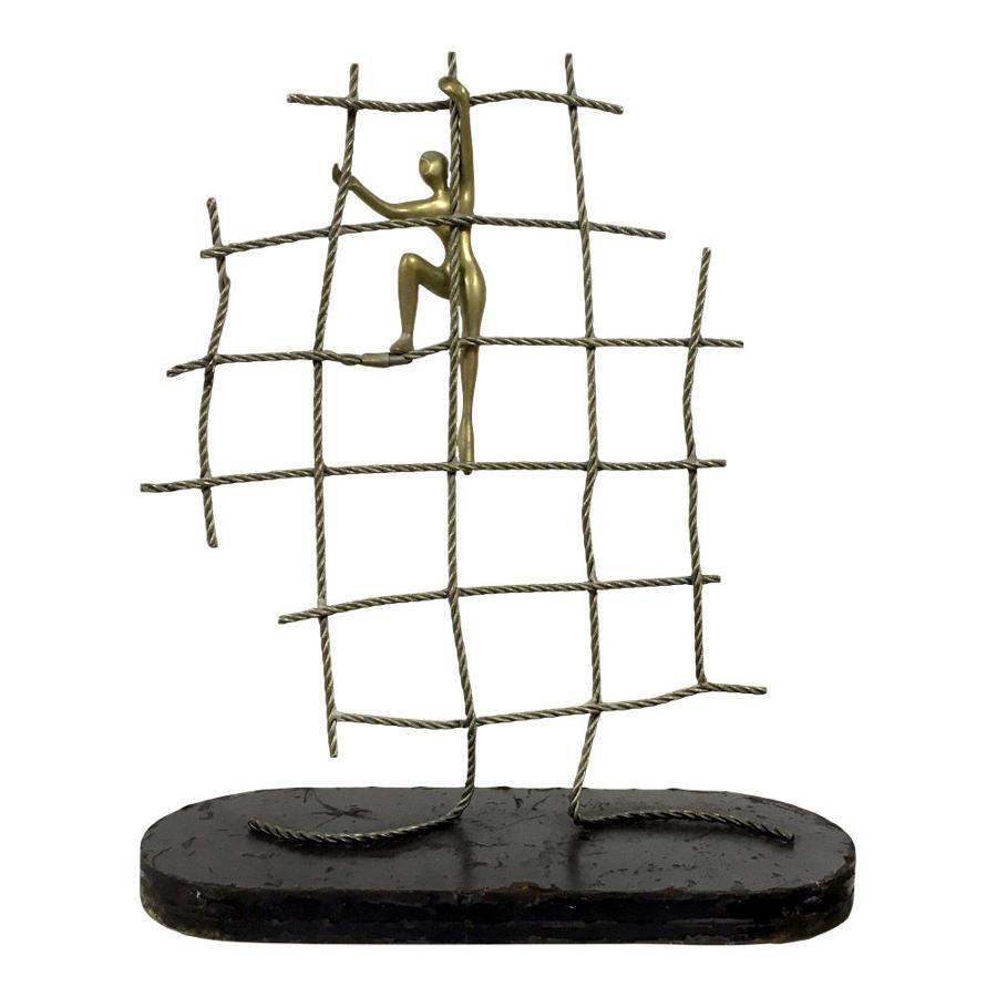 Abstract brass figure climbing up a net